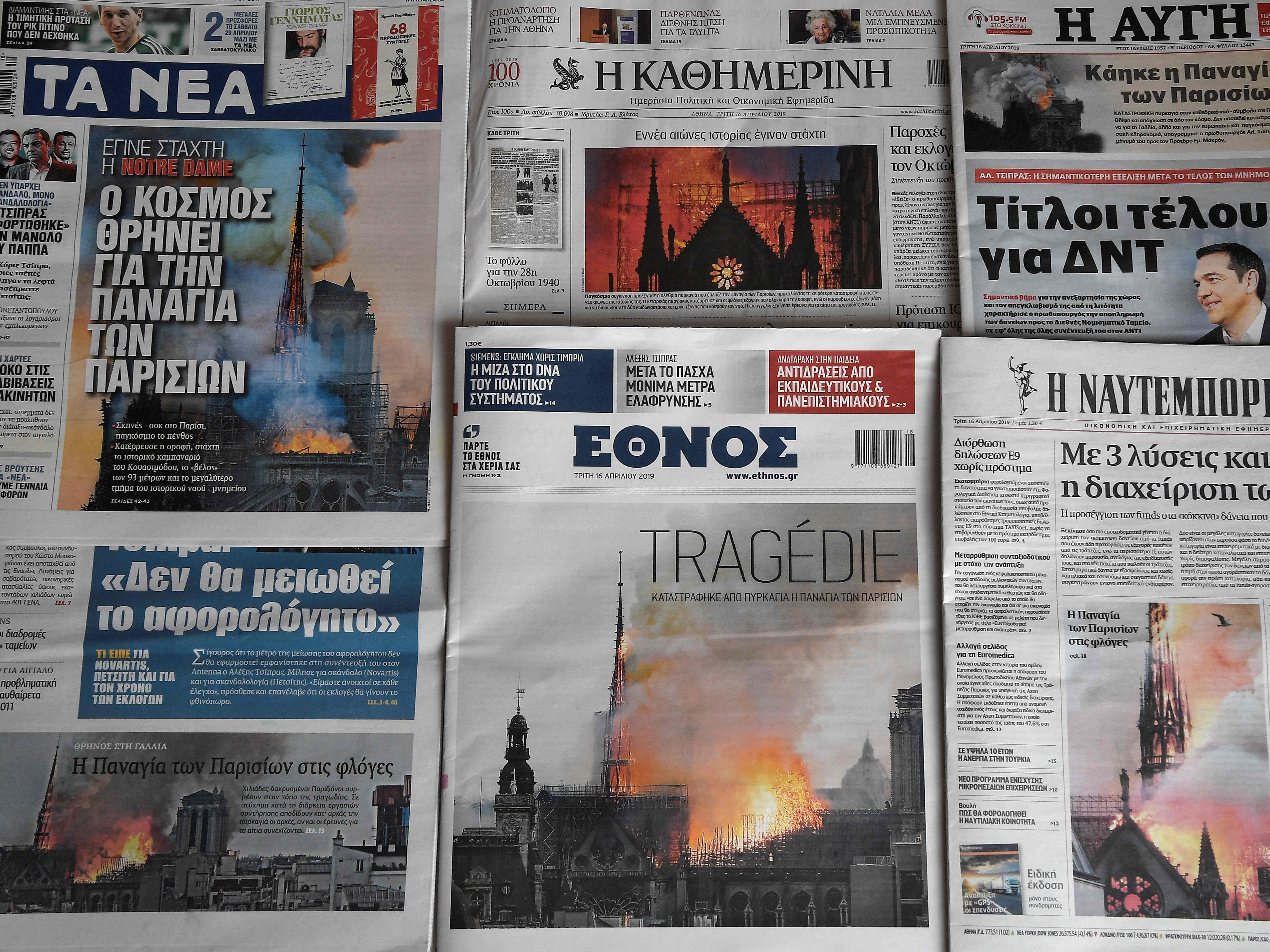 Greek newspapers with images of the landmark Notre Dame Cathedral in Paris in flames are pictured in Athens on April 16, 2019, the day after a fire ripped through its roof.