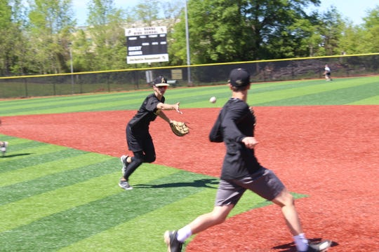 T.L. Hanna senior first baseman makes the flip to sophomore pitcher Brian Boone during a practice before their spring break tournament trip.