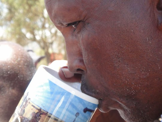 A man drinks from a cup of water from the well in Namelok, Kenya, that was made possible by members of First Central Presbyterian Church.