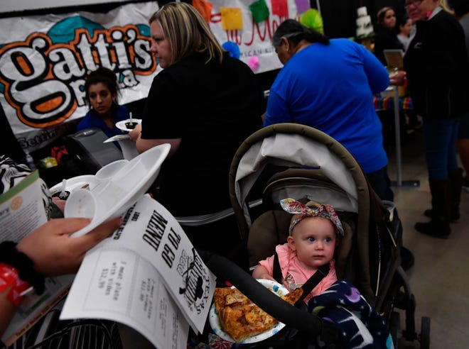 Willow Daino looks up from her pizza as her Aunt Selena cruises through the Taste of Abilene on Tuesday in the Abilene Convention Center.
