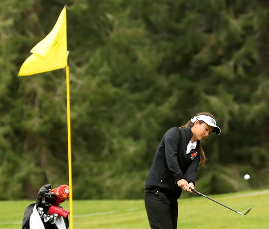 Central Kitsap golfer Brittany Kwon chips a shot onto the green during a match against Shelton at Gold Mountain Golf Club on Tuesday, April 16, 2019. Kwon is a three-time defending Class 3A state champion.