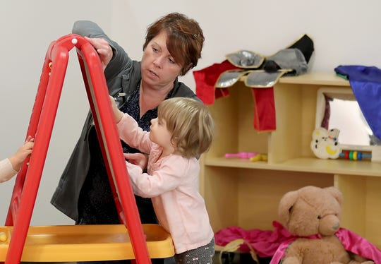 Special educator Anne Marie Adams works with Ellorie Baker, 2, at Holly Ridge in Bremerton on Wednesday. The nonprofit that provides services to children birth through 3 has taken over its new building on Kitsap Way.