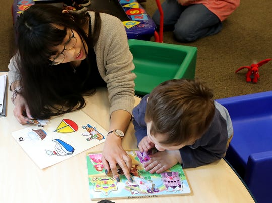 Meryl Sanchez, speech and language pathologist assistant, helps a youngster with a puzzle at Holly Ridge in Bremerton on Wednesday. Classrooms in its new building at Kitsap Way are larger, let in more light, and allow more permanent setups for the various programs the nonprofit offers.