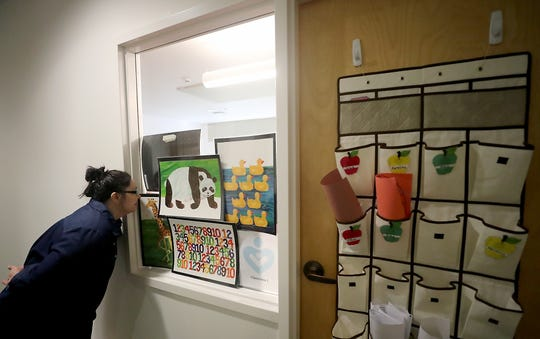 Jerra Baker sneaks a peek through the gaps in the posters of the window where her daughter Ellorie, 2, attends the Infant Toddler Program at Holly Ridge in Bremerton on Wednesday.