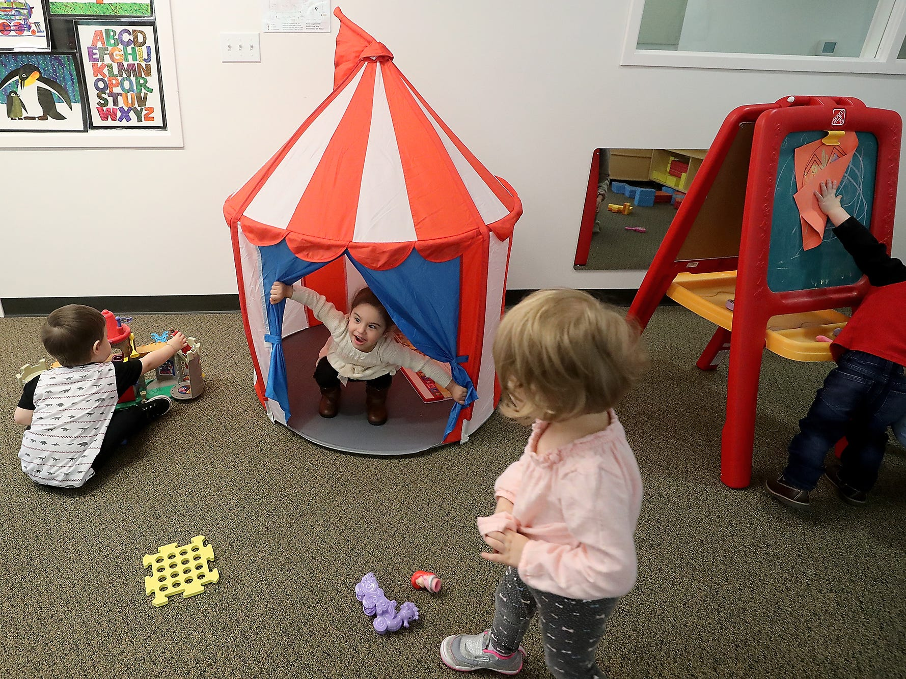 Rosalie Medina, 2, center, peeks out of a small circus tent while playing with classmates at Holly Ridge in Bremerton on Wednesday, April 16, 2019.