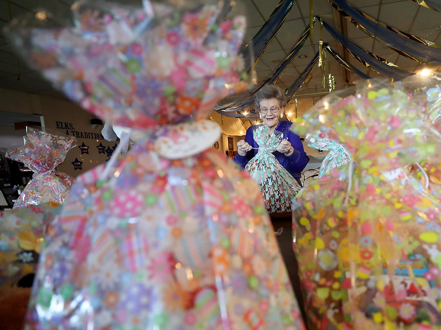 Misty Davis, chairman of the Easter Egg Hunt Committee, smiles while tying the tops of the easter basket bundles that will be prizes for those who find the golden eggs, as she and fellow Elks get baskets and eggs ready for the upcoming Easter Egg Hunt at the Elks Lodge in Bremerton on Wednesday, April 16, 2019.