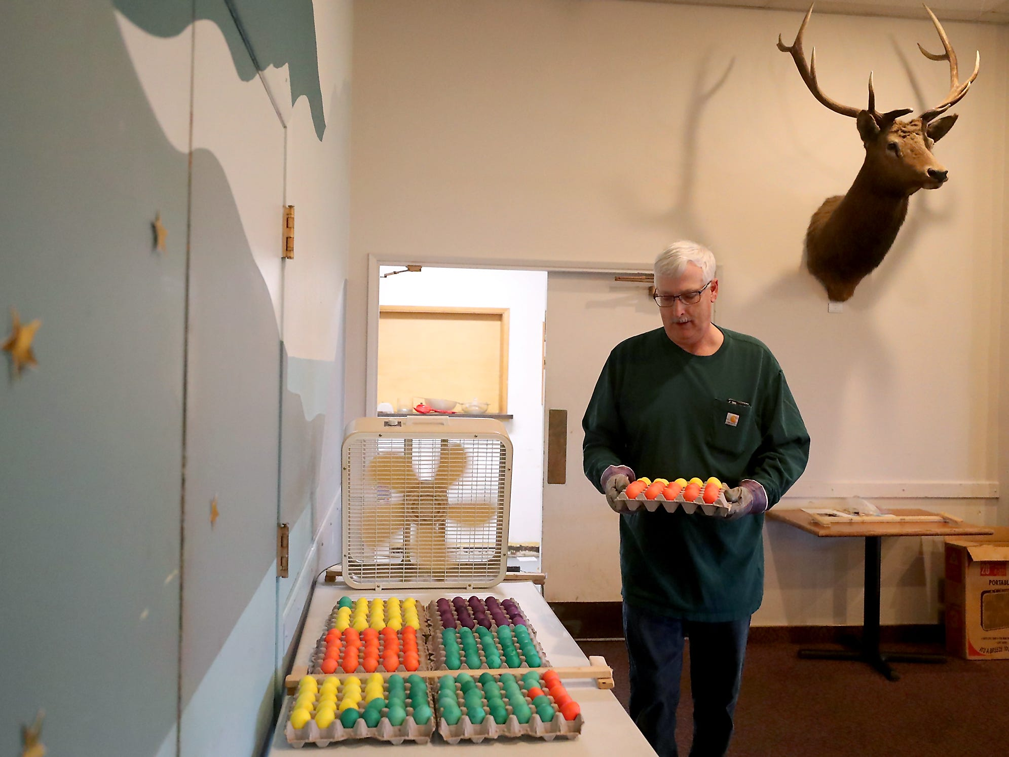Bob Carter carries a carton of dyed eggs to the drying table as he and fellow Elks members dye eggs, put baskets together and fill plastic eggs with candy in preparation for the upcoming Easter Egg Hunt, at the Elks Lodge in Bremerton on Wednesday, April 16, 2019. Volunteers were preparing 3,000 eggs for the hunt.