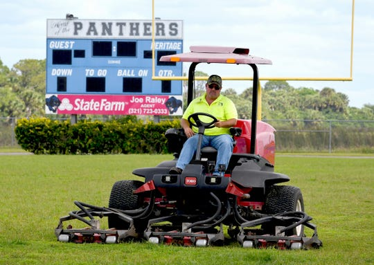 With so few employees and a tight budget to mow the grass and athletic fields, the Brevard school district's facilities team has been struggling to keep up, which sometimes results in tall, unruly grass. Photos shows equipment operator Derek Bissett mowing the football field at Heritage High School.