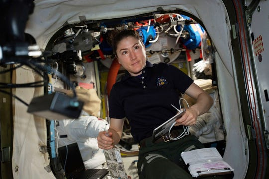 In this April 8, 2019 photo made available by NASA, astronaut and Expedition 59 Flight Engineer Christina Koch works on U.S. spacesuits inside the Quest airlock of the International Space Station. Koch will remain on board until February 2020.