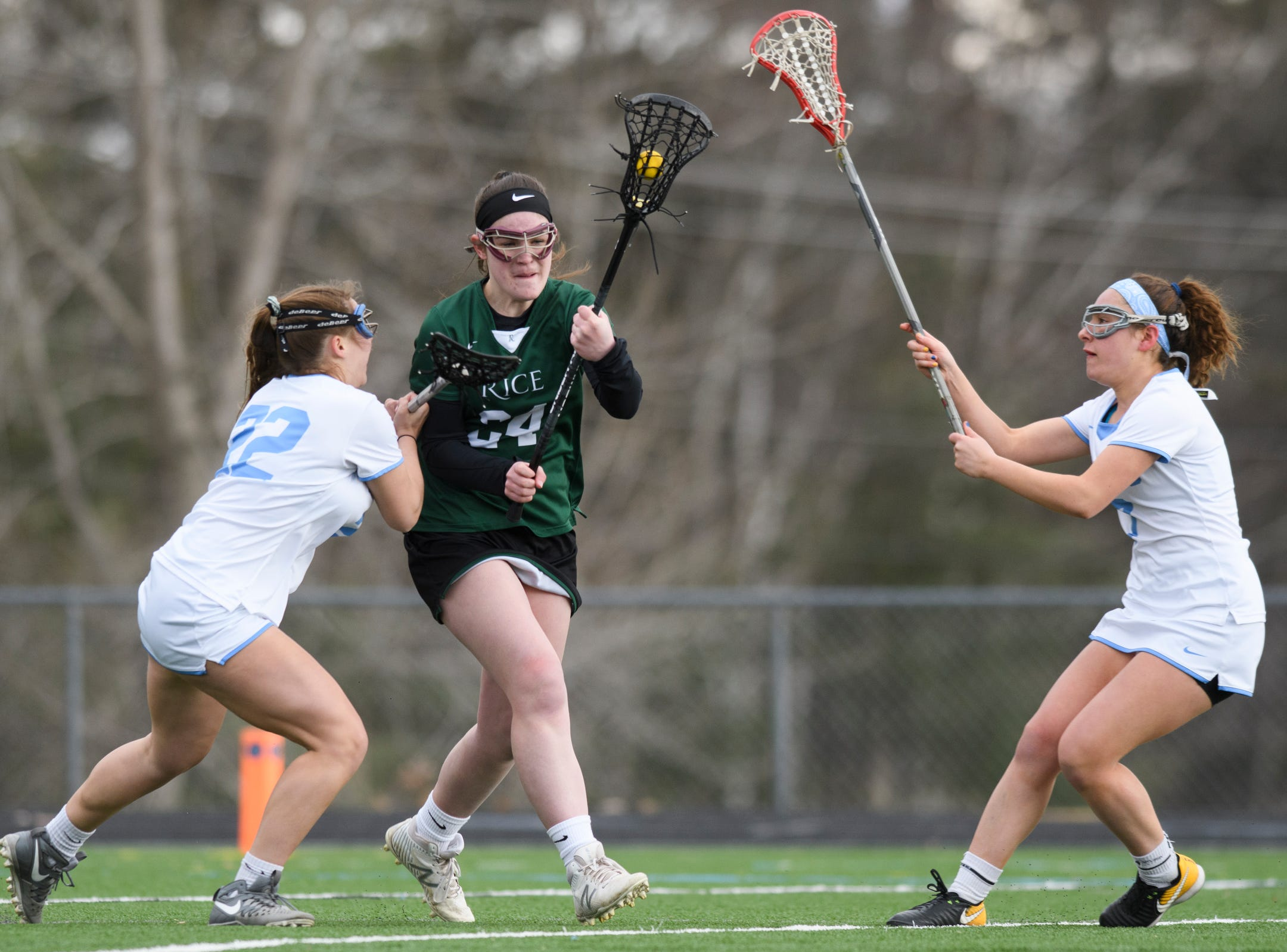 Rice's Annika Hanson (24) runs between South Burlington's Sabrina Redzic (22) and Caroline Desautels (13) during the girls lacrosse game between the Rice Green Knights and the South Burlington Wolves at South Burlington High School on Tuesday afternoon April 16, 2019 in South Burlington, Vermont.