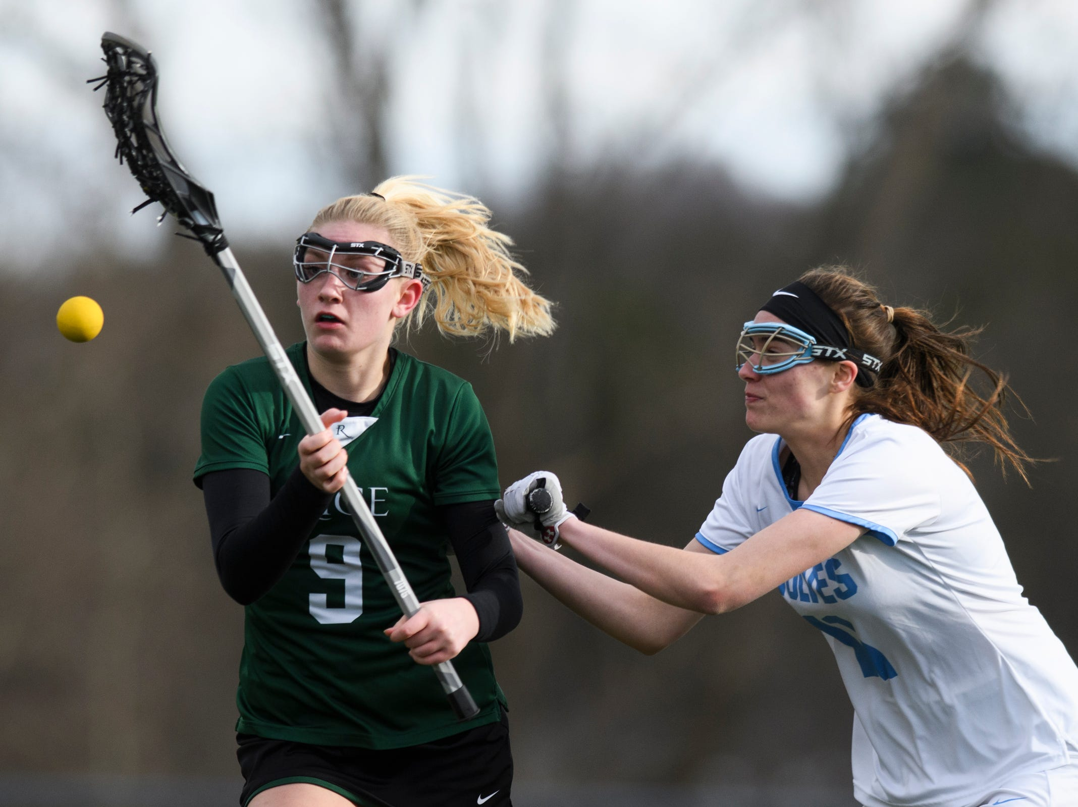 South Burlington's Christina March (11) knocks the ball out of the stick of Rice's Alex Dostie (9) during the girls lacrosse game between the Rice Green Knights and the South Burlington Wolves at South Burlington High School on Tuesday afternoon April 16, 2019 in South Burlington, Vermont.