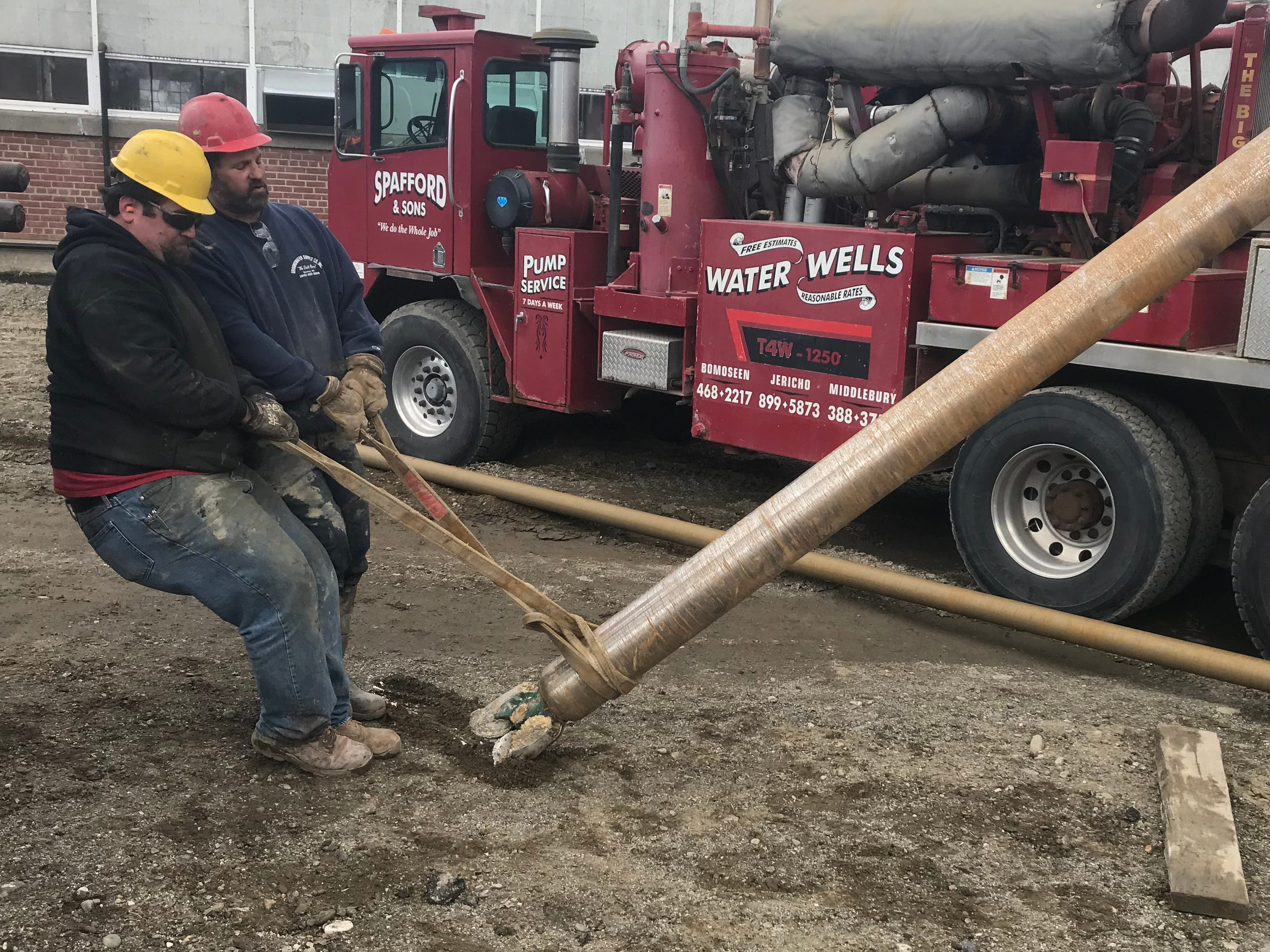 Bret (left) and Tim Williams, co-owners of Spafford & Sons Water Wells, move a drilling shaft at Hula Lakeside — the former Blodgett Ovens factory — in Burlington on Tuesday, April 16, 2019.