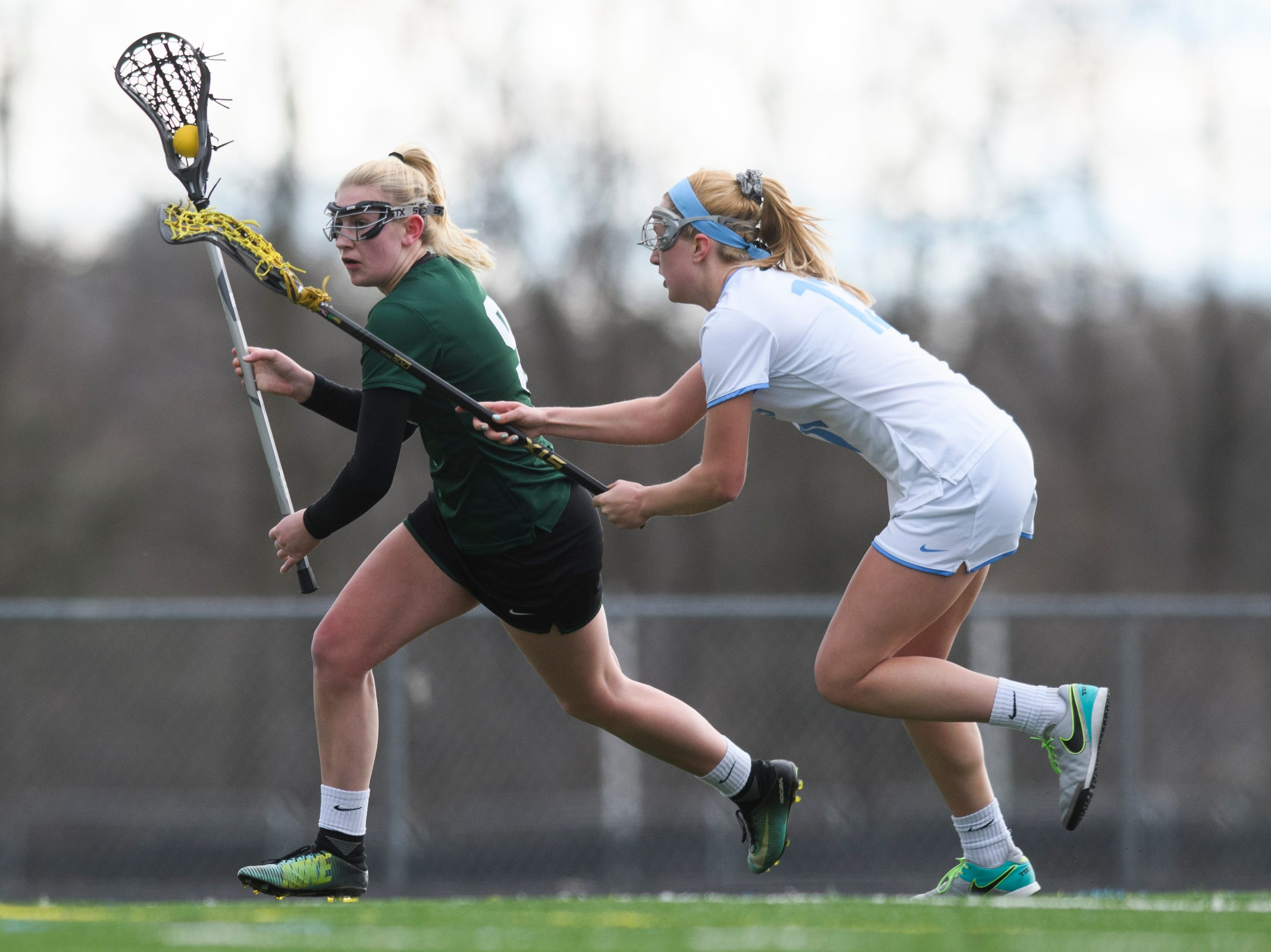 Rice's Alex Dostie (9) runs down the field with the ball past South Burlington's Caroline Desautels (13) during the girls lacrosse game between the Rice Green Knights and the South Burlington Wolves at South Burlington High School on Tuesday afternoon April 16, 2019 in South Burlington, Vermont.