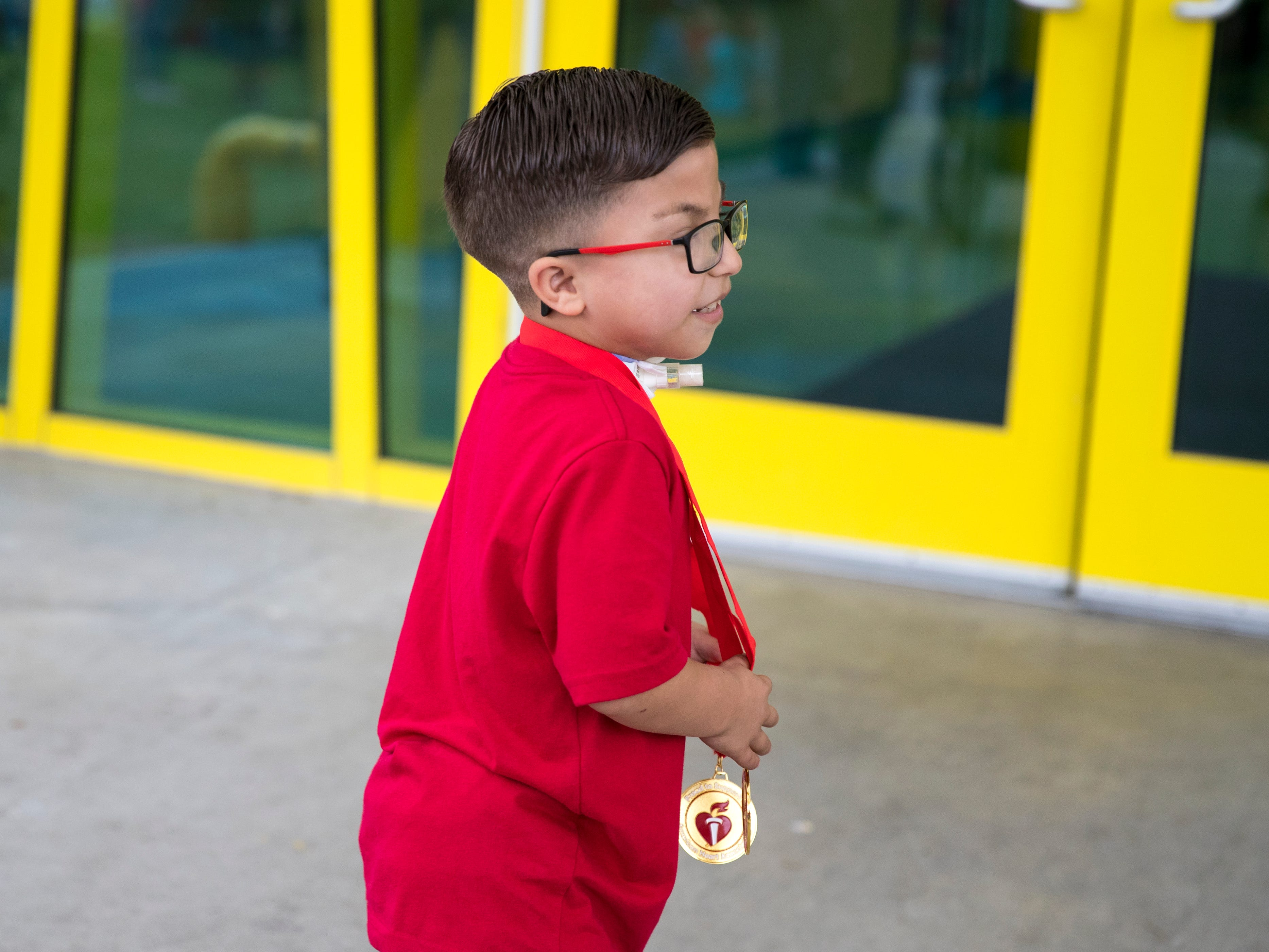 """Ethann Valdez, 9, leads a parade back into the school at Garcia Elementary School on Wednesday, April 17, 2019. Diagnosed at the age of five with geleophysic dysplasia (known as dwarfism), Ethann will be out of school for the rest of the year as he undergoes open heart surgery for a valve replacement to the main aorta of his heart. The school wanted to send him off with a """"Best Wishes Parade"""" before he left."""