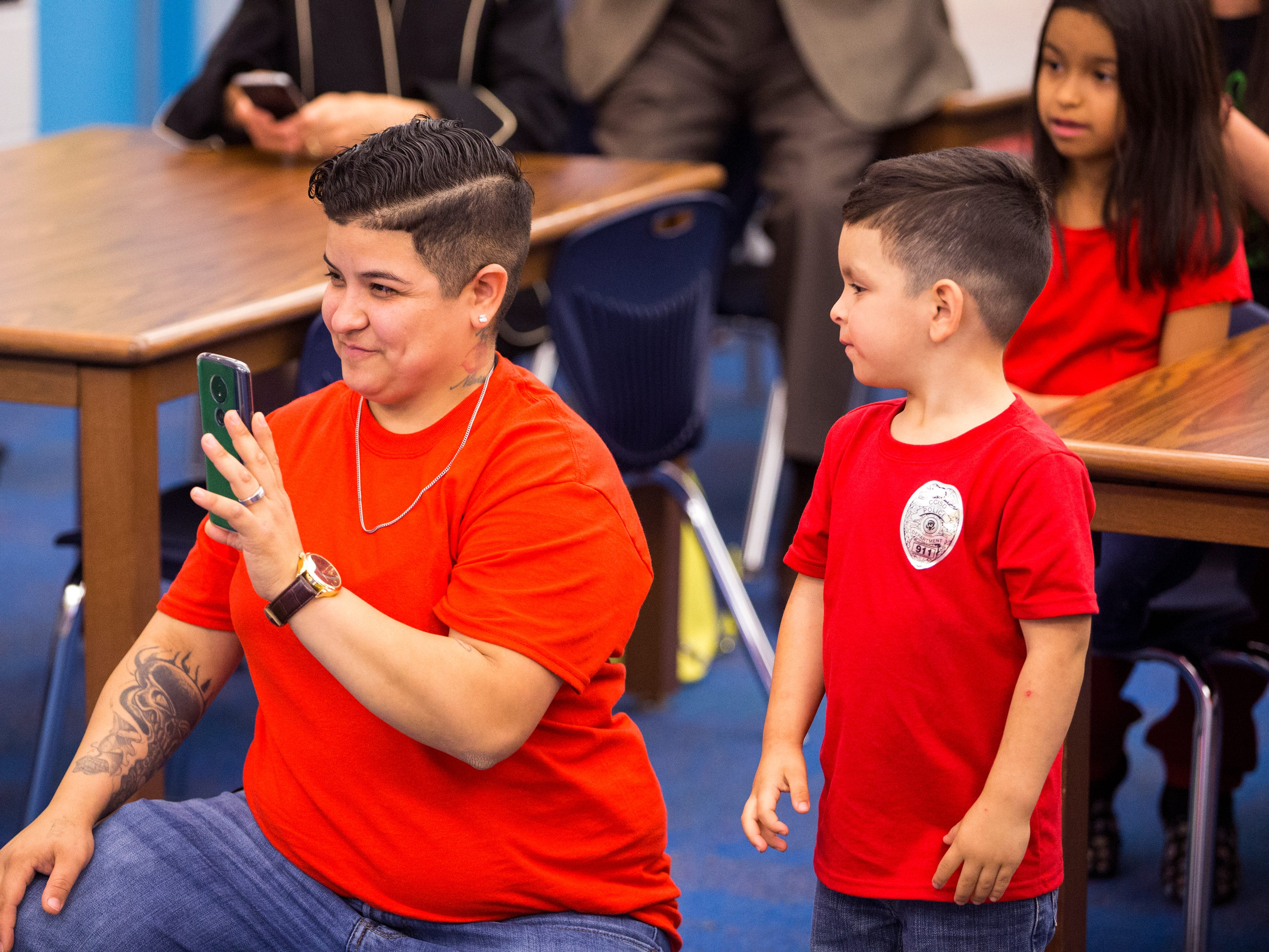 """Roberta Hernandez (left) and Calvin Hernandez, 3, watch while Ethann Valdez, 9, is surprised with a message from a television personality on """"Ghost Hunters"""" folliwing a parade in Ethann's honor at Garcia Elementary School on Wednesday, April 17, 2019. Diagnosed at the age of five with geleophysic dysplasia (known as dwarfism), Ethann will be out of school for the rest of the year as he undergoes open heart surgery for a valve replacement to the main aorta of his heart. The school wanted to send him off with a """"Best Wishes Parade"""" before he left."""