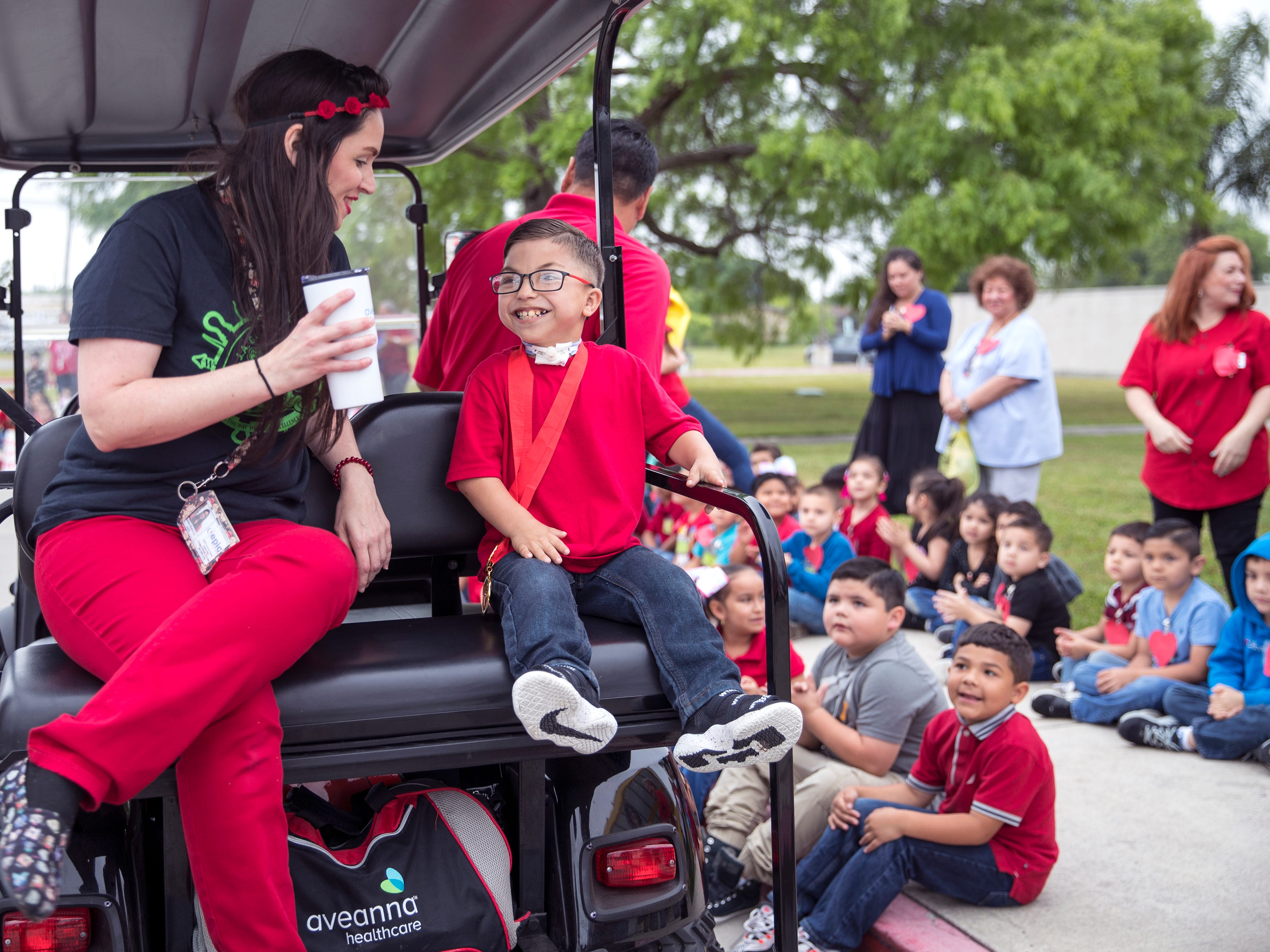 """Janine Hobrecht (left), a pediatric private duty nurse, talks with Ethann Valdez, 9, before a parade begins in his honor at Garcia Elementary School on Wednesday, April 17, 2019. Diagnosed at the age of five with geleophysic dysplasia (known as dwarfism), Ethann will be out of school for the rest of the year as he undergoes open heart surgery for a valve replacement to the main aorta of his heart. The school wanted to send him off with a """"Best Wishes Parade"""" before he left."""