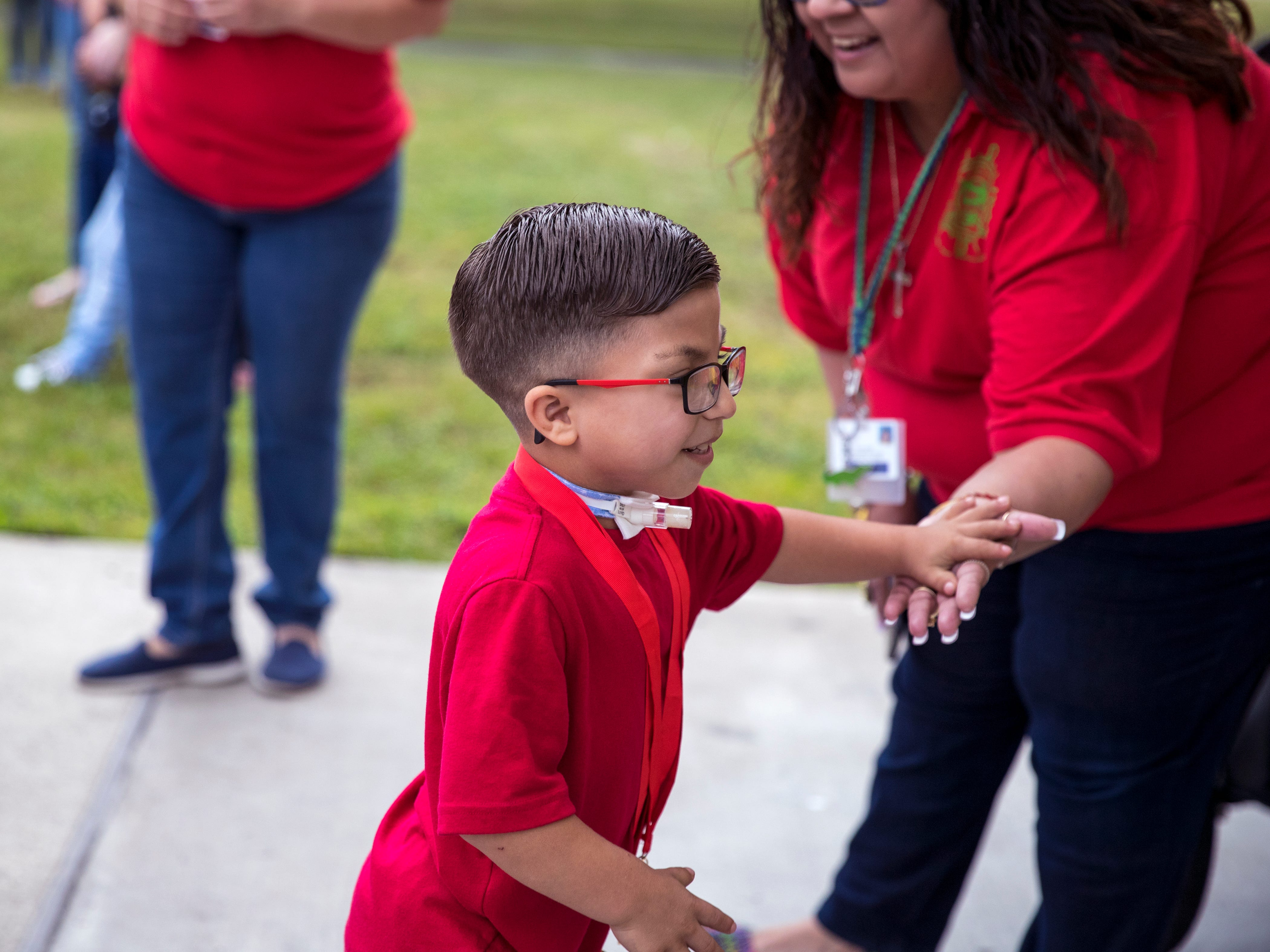 """Ethann Valdez, 9, gets a high-five as he leads the parade back into the school at Garcia Elementary School on Wednesday, April 17, 2019. Diagnosed at the age of five with geleophysic dysplasia (known as dwarfism), Ethann will be out of school for the rest of the year as he undergoes open heart surgery for a valve replacement to the main aorta of his heart. The school wanted to send him off with a """"Best Wishes Parade"""" before he left."""
