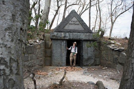 Rocky Wilson, a longtime Camden resident, poet, teacher and Walt Whitman impersonator stands by Whitman's gravesite at Harleigh Cemetery in Camden, N.J Thursday, April 11, 2019.
