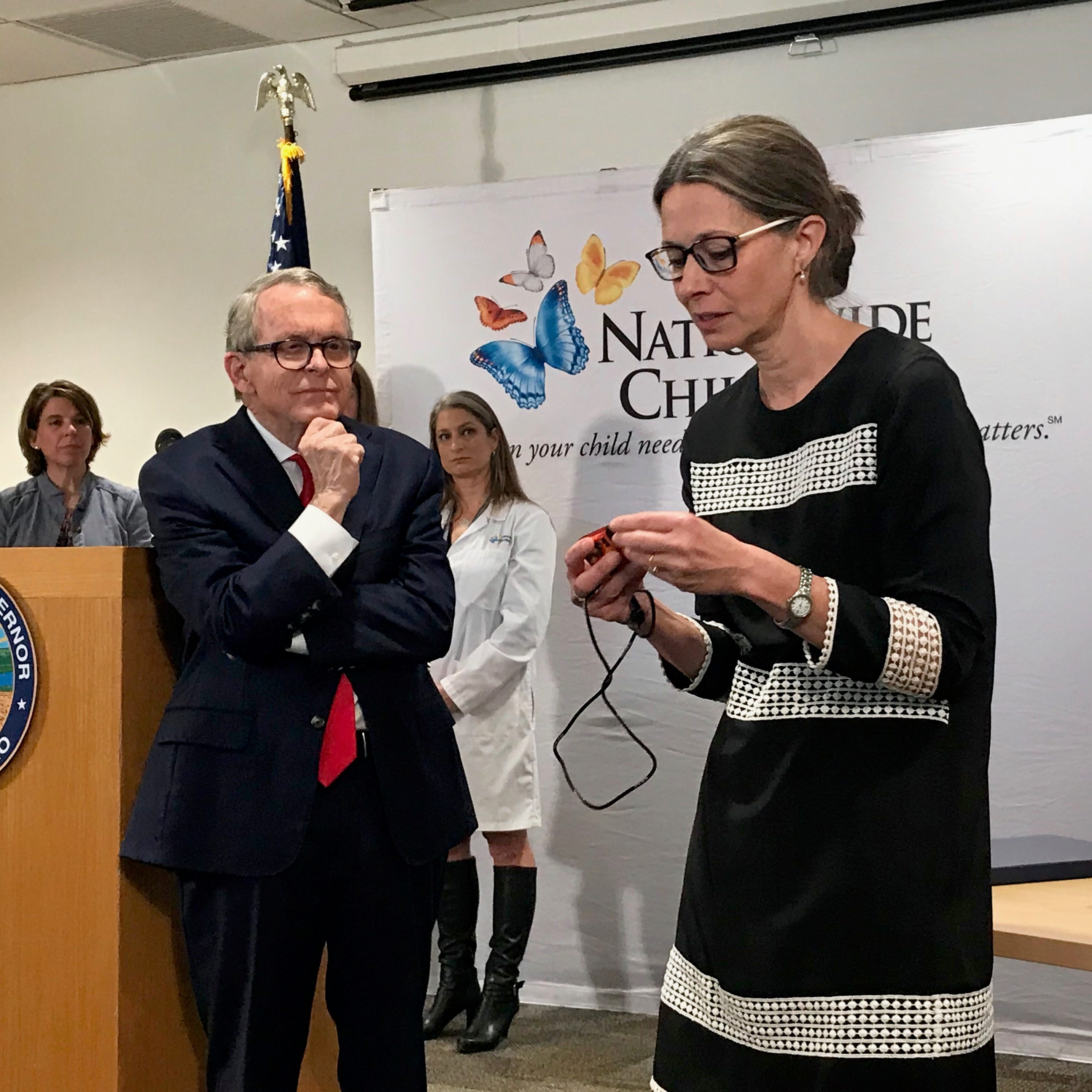 Ohio Gov. Mike DeWine watches Ohio Department of Health Director Amy Acton explain how small vaping devices work at a news conference at Nationwide Children's Hospital in Columbus on April, 17, 2019.