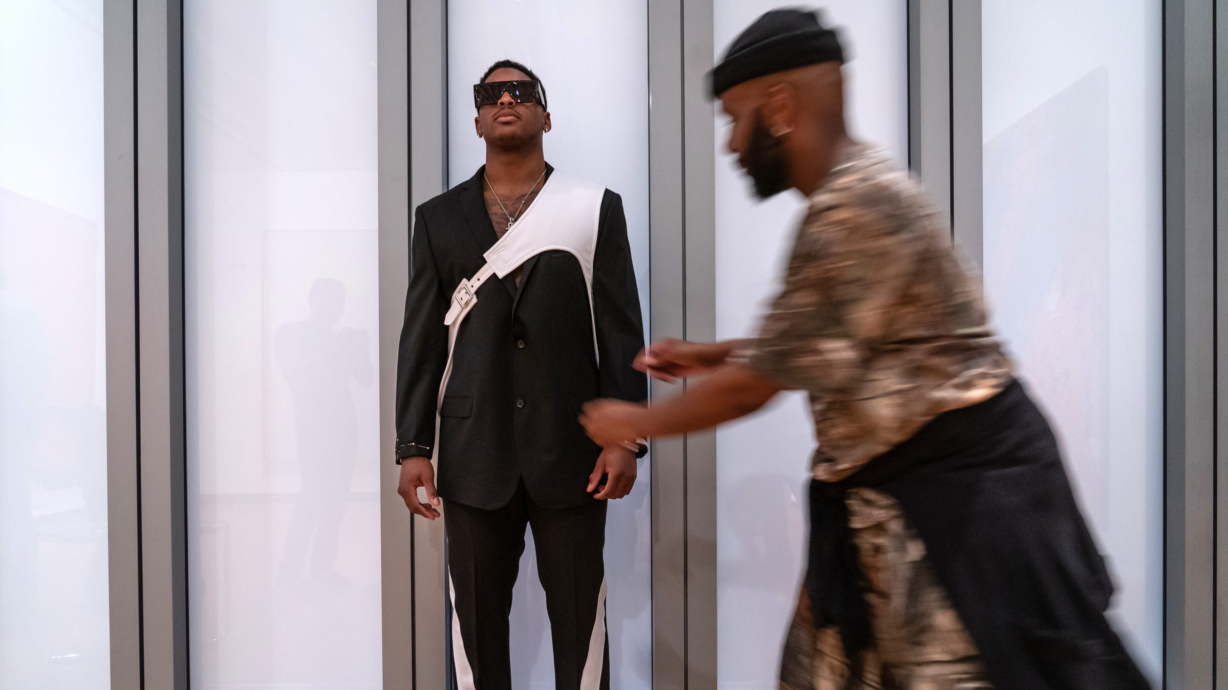 University of Michigan linebacker Devin Bush Jr. stands in his selection of suits to wear for the NFL draft as designer Jatannio moves in to make adjustments at the University of Michigan Museum of Art in Ann Arbor on 2019.