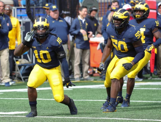 Michigan defenders Devin Bush (10) and Michael Dwumfour (50) celebrate after a stop against Nebraska during first half action Saturday, September 22, 2018 at Michigan Stadium in Ann Arbor, Mich.