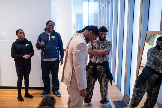 University of Michigan linebacker Devin Bush Jr. (center) looks down to pants being fitted as his girlfriend Carissa Martin of Detroit looks on with his father Devin Bush Sr. and fashion designer Jatannio while trying on suits to select for the NFL draft at the University of Michigan Museum of Art in Ann Arbor on Friday, April 5, 2019.