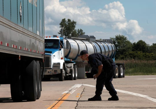 Officer Doug Dowdy inspects the rear axle on a Truck after being stopped for a safety belt violation while going through the weigh station on northbound I-75 in Monroe on Thursday, July 25, 2013.  Jessica J. Trevino/Detroit Free Press