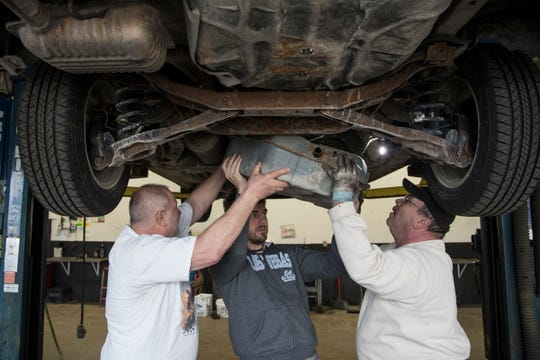 Under a lift, from left, Jerry Carson, his son Andrew, both of Canton, with their friend Dewie Smith of Northville, carefully drop the gas tank off Andrew's 2007 Ford Focus at My Mechanics Place in Livonia, Thursday, April 11, 2019. They have to remove the gas tank from the car in order to replace the fuel pump.