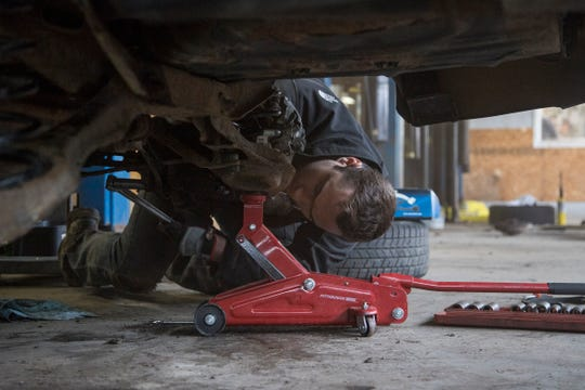 Patrick Denny tries to remove a stuck bolt on his 2006 Ford Focus at My Mechanics Place in Livonia, Thursday, April 11, 2019. His car is supported by two jack stands. (not in the photo) Denny lives in an apartment in Detroit, does not have a garage to work on his car.