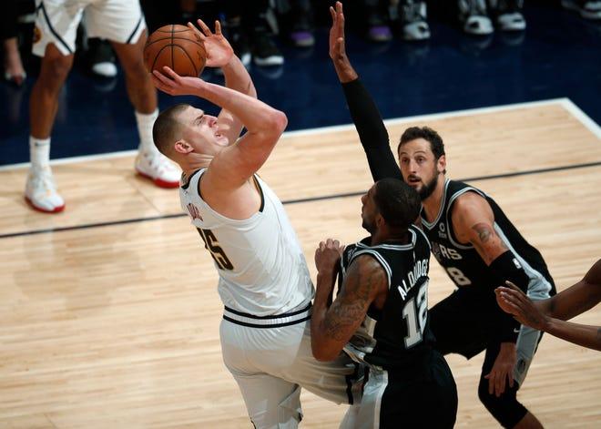 Denver Nuggets center Nikola Jokic, left, shoots over San Antonio Spurs center LaMarcus Aldridge (12) and guard Marco Belinelli in the second half.