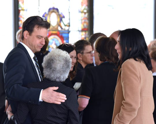 Detroit News Managing Editor Gary Miles, left, and his wife, Dorothy, right, console Debbie Lamm, widow of the late Detroit News Editor and Publisher Jon Wolman after the funeral service.