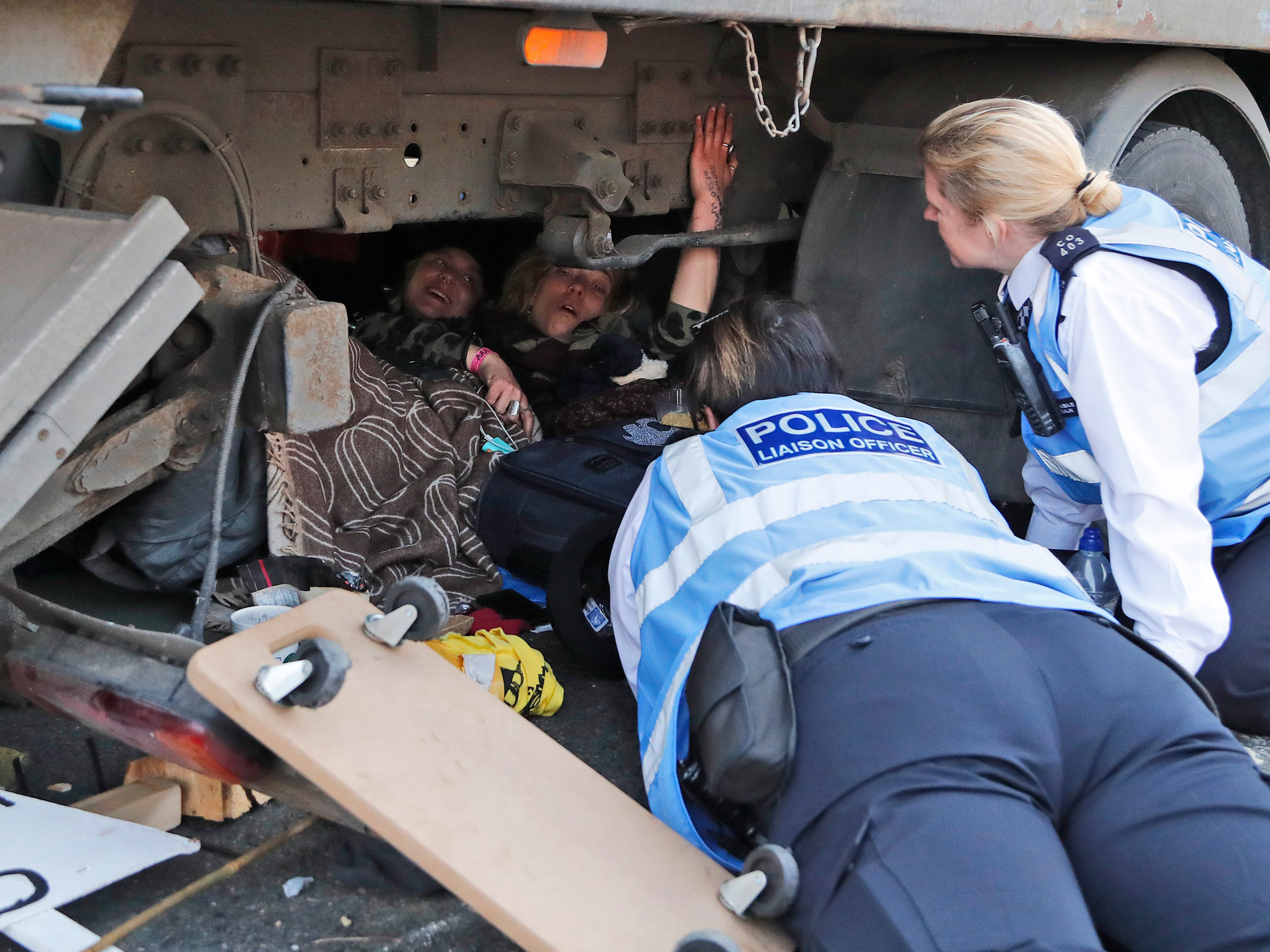 Police officers speak to protesters under a lorry, during a civic disobedience event to block Waterloo Bridge in London, Wednesday, April 17, 2019. The group Extinction Rebellion is calling for a week of civil disobedience against what it says is the failure to tackle the causes of climate change.