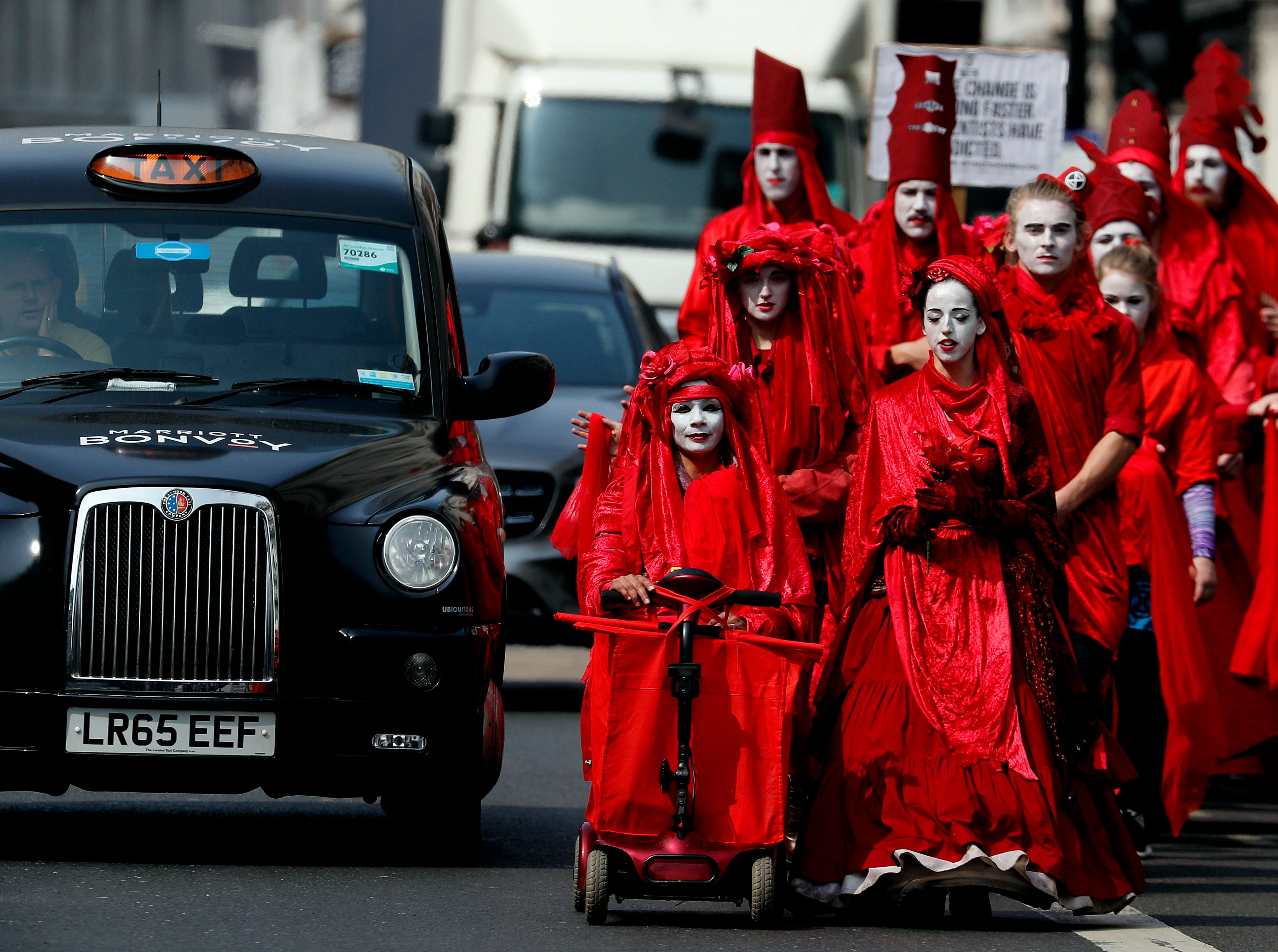 Members of the so called 'Red Brigade' march in disobedience on the street from Oxford Circus to Piccadilly Circus to protest in London, Wednesday, April 17, 2019. The group Extinction Rebellion is calling for a week of civil disobedience against what it says is the failure to tackle the causes of climate change.