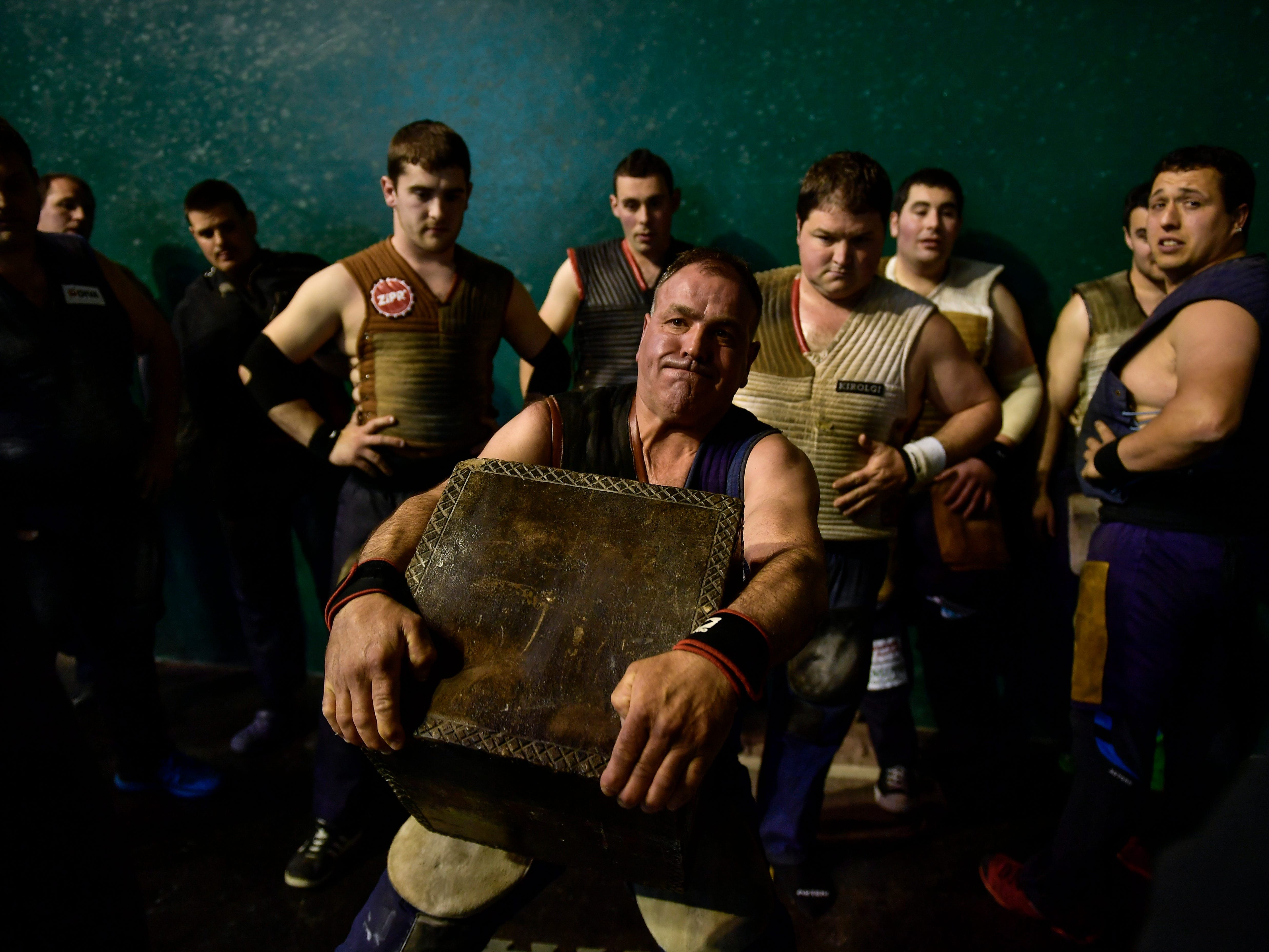 """Jose Ramon Izeta, 52, a former basque stone lifter, holds a 100 kilograms stone, during an exhibition in the basque village of Azkoitia, northern Spain.  The """"Harri-jasotze,"""" or """"Stone Lifters"""" in the local language of the mountainous Basque Country region, faces contorted by the effort these burly competitors strain to lift massive weights as many times as they can."""