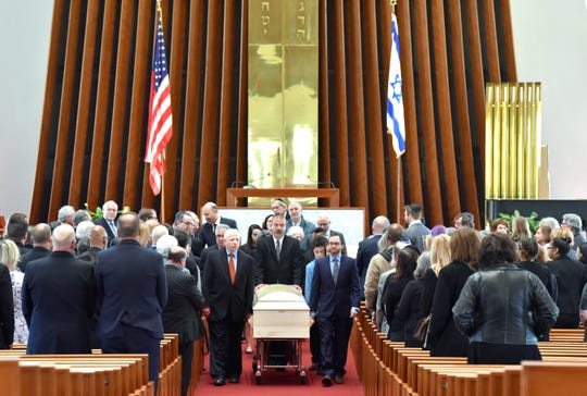 Pallbearers carry Jon Wolman's casket to the hearse as they pass by family members and friends inside Temple Beth El.