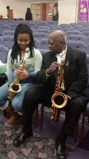 Ira Heyward Sr. with the granddaughter of friend George Nickens at Faith Temple Church in Elmira. Heyward was an accomplished musician.