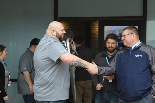 Terrasana Labs General Manager Dan Stotridge, left shakes hands with Bob Gross, Fremont Economic Development Director, right, as the medical marijuana facility opened Wednesday.