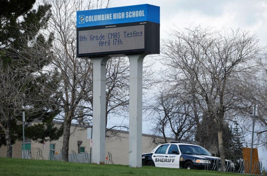 "A patrol car is parked in front of Columbine High School, Wednesday, April 17, 2019, in Littleton, Colo., where two student killed 12 classmates and a teacher in 1999. The school was closed along with hundreds of others in Colorado after an armed young Florida woman who was allegedly ""infatuated"" with Columbine threatened violence just days ahead of the 20th anniversary of the attack."