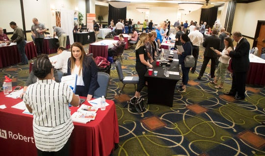 Holly Cunard, second from left, Assistant Vice President for Office Team, a Robert Half Company talks to a job seeker at a job fair at the Crowne Plaza hotel at the Bell Tower Shops on Wednesday April 17, 2019. Dozens of companies are seeking workers to fill positions.
