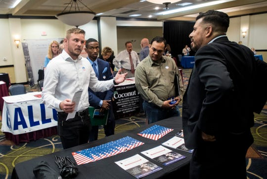 Helbert Asprilla, right, a warriors to work specialist for the Wounded Warrior Project talks to, from left, Matthew Niezelski, John Carr and Christopher Hengel at a job fair at the Crowne Plaza hotel at the Bell Tower Shops in Fort Myers on Wednesday April 17, 2019. Dozens of companies are seeking workers to fill positions. Niezelski,  veteran of the Marine Corp, Carr is a veteran of the U.S. Air Force and Hengel is a veteran of the Marine Corp.