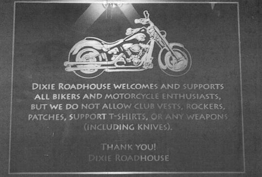 A photo included with a letter from Dixie Roadhouse's attorney shows a sign about the no biker colors policy posted at the nightclub.