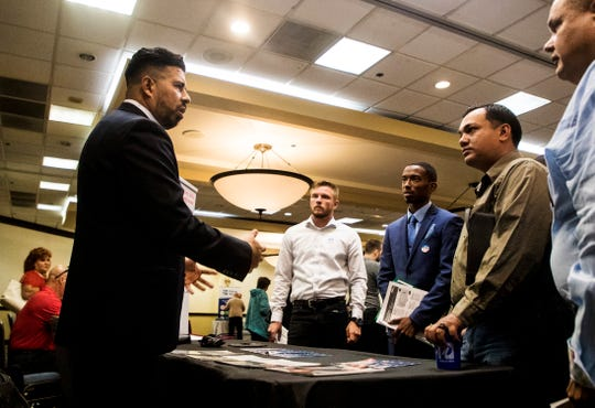 Helbert Asprilla, left, a warriors to work specialist for the Wounded Warrior Project talks to prospective job seekers, from left, Matthew Niezelski, John Carr and Christopher Hengel at a job fair at the Crowne Plaza hotel at the Bell Tower Shops in Fort Myers on Wednesday April 17, 2019. Dozens of companies are seeking workers to fill positions. Niezelski,  veteran of the Marine Corp, Carr is a veteran of the U.S. Air Force and Hengel is a veteran of the Marine Corp.