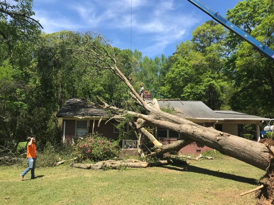 A tree lies across the roof of Donna Robertson and Darlene Strickland's home in Simpsonville after a tornado ripped through the area on Sunday night.