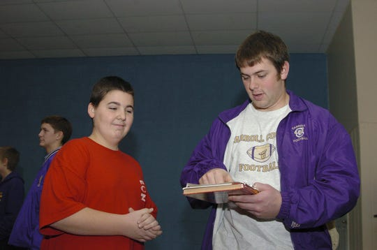 """Former CMR football standout Chris Ramstead signs an autograph for 13-year-old Nathan McCain at Pickwick South Elementary School in Savannah, Tenn., on Dec. 15, 2005. The Carroll College Saints visited the school as part of the NAIA's """"Character Counts"""" program to encourage kids to stay in school, stay away from drugs, and participate in school and community activities."""