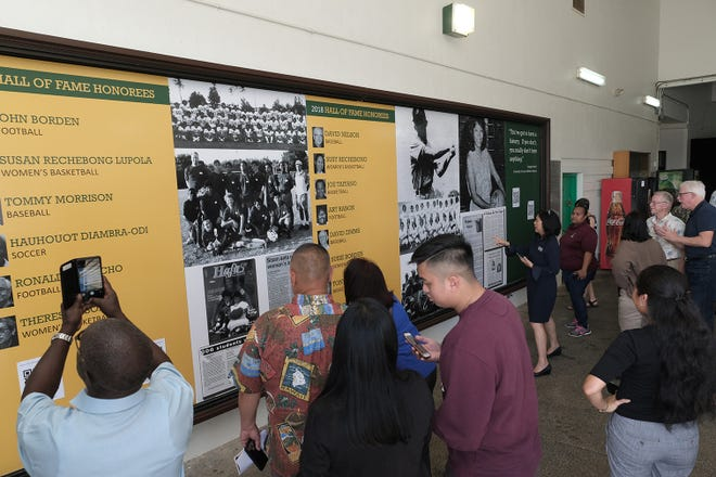 A crowd examines the Wall of Fame at University of Guam Tuesday