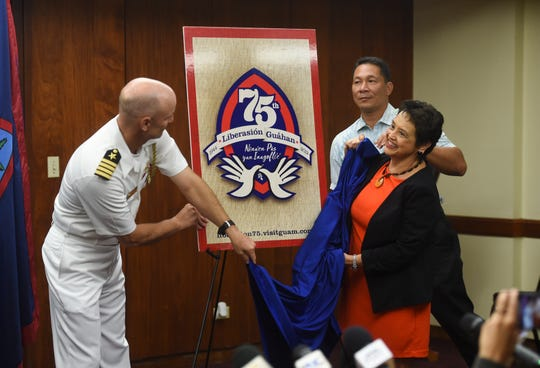 Gov. Lou Leon Guerrero and Capt. Hans Sholley, left, with the assistance of the governor's chief of staff, Tony Babauta, unveil the 75th Guam Liberation logo during a press conference at the Ricardo J. Bordallo Governor's Complex in Adelup, April 17, 2019.