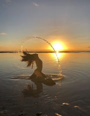 Photo of Amanda Salas' daughter soaking in the saltwater with a sunset in the background at Gun Beach in Tumon. Photo taken on April 11, 2019.