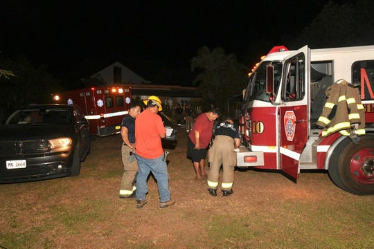 Fire investigators gather information after a blaze near Wusstig Road in Dededo Wednesday night.