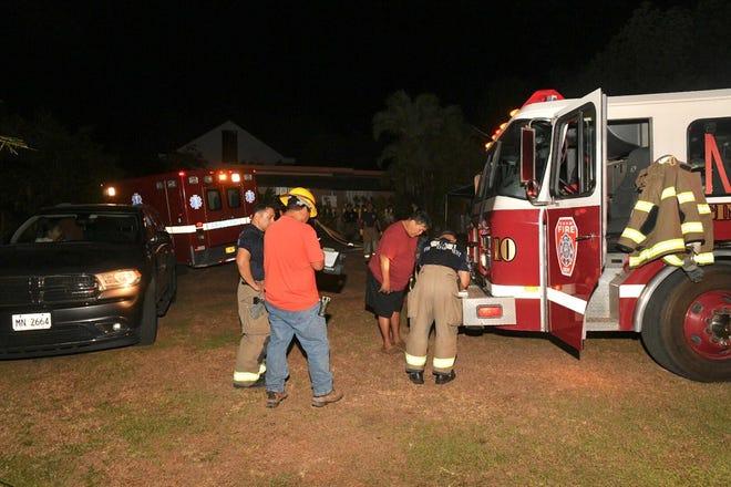 Fire investigators gather information after a blaze near Wusstig Road in Dededo Wednesday night.