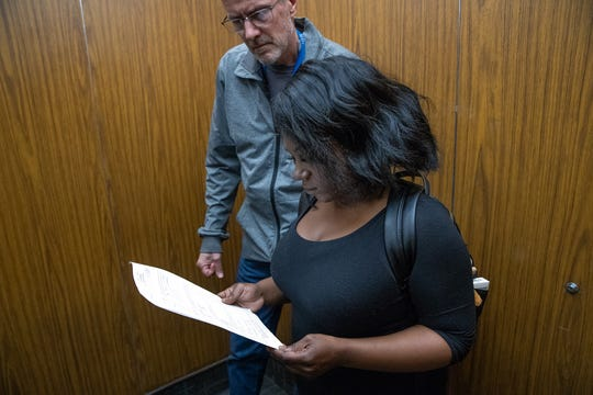 Ashley Peterson reads a document with her father, Craig, in the elevator up to the fourth floor of the Madison County Government Center and Courts in Anderson, Ind., on Monday, April 8, 2019.